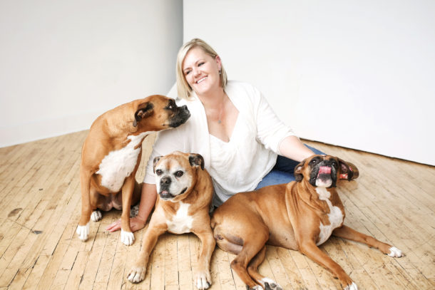 happy dog mom jennifer waters sitting with three boxer dogs